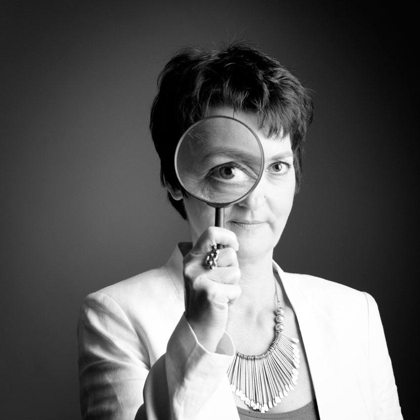 Porträt Heide Liebmann mit Lupe vor dem linken Auge