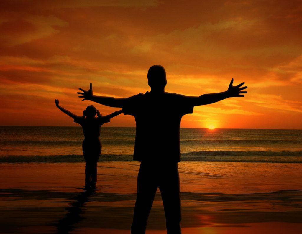 Frau und Mann mit ausgebreiteten Armen vor untergehender Sonne am Meer