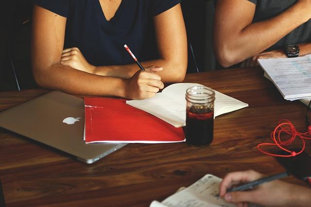 Unterarme mit Schreibzeug und Laptop auf Holztisch