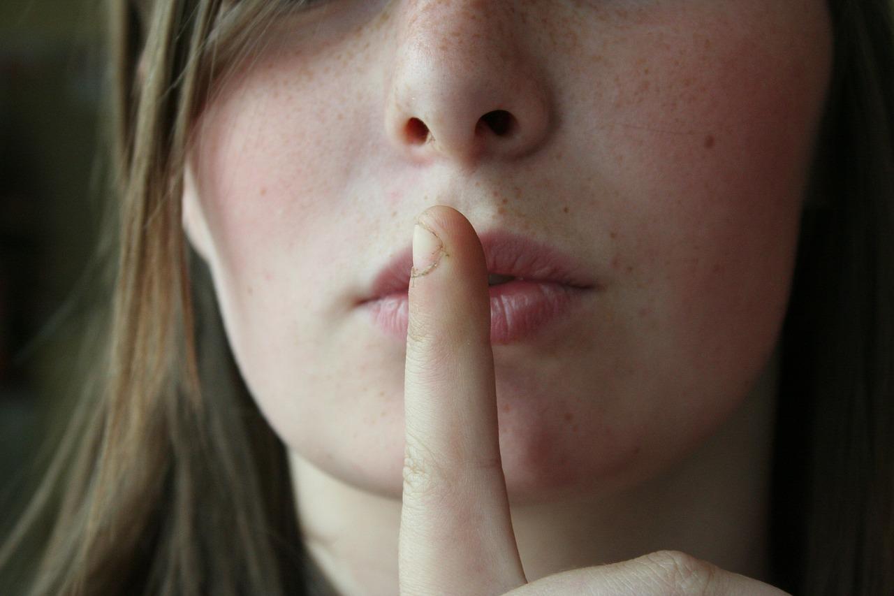 Frau legt Finger auf die Lippen