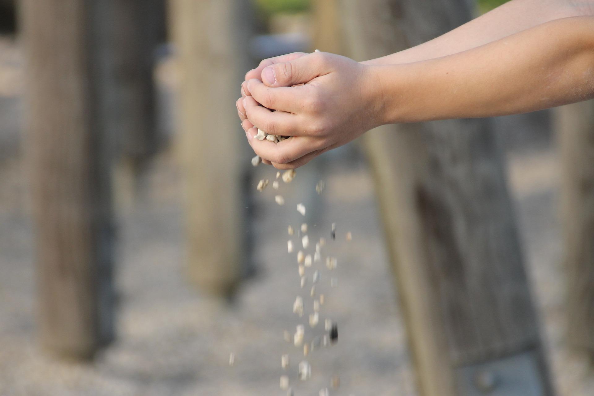 Verschränkte Hände, aus denen Steinchen rieseln