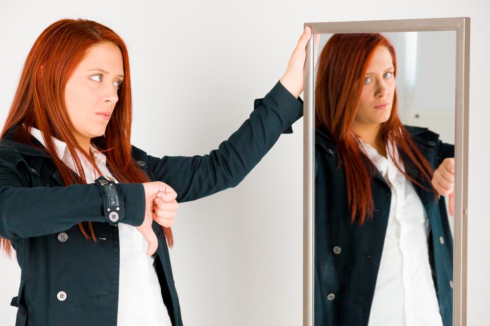 Frau im Spiegel zeigt sich Daumen runter
