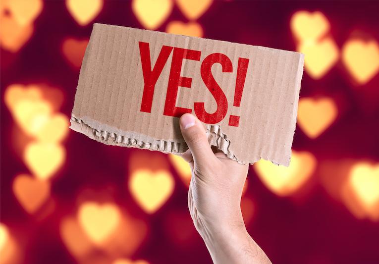 """Hand mit Schild, auf dem """"YES!"""" steht vor leuchtenden Herzen im Hintergrund"""