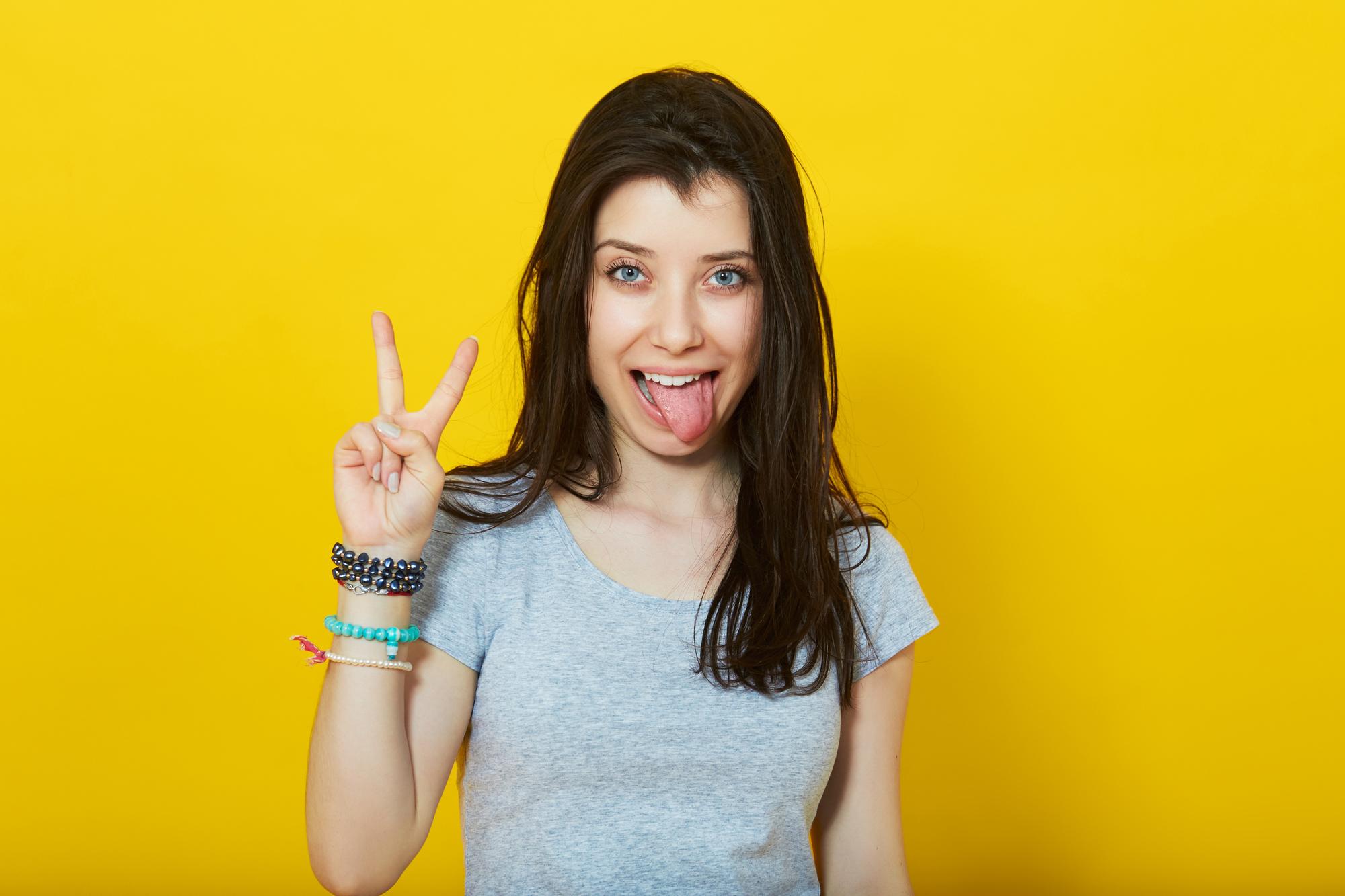 junge Frau macht Victoryzeichen mit herausgestreckter Zunge