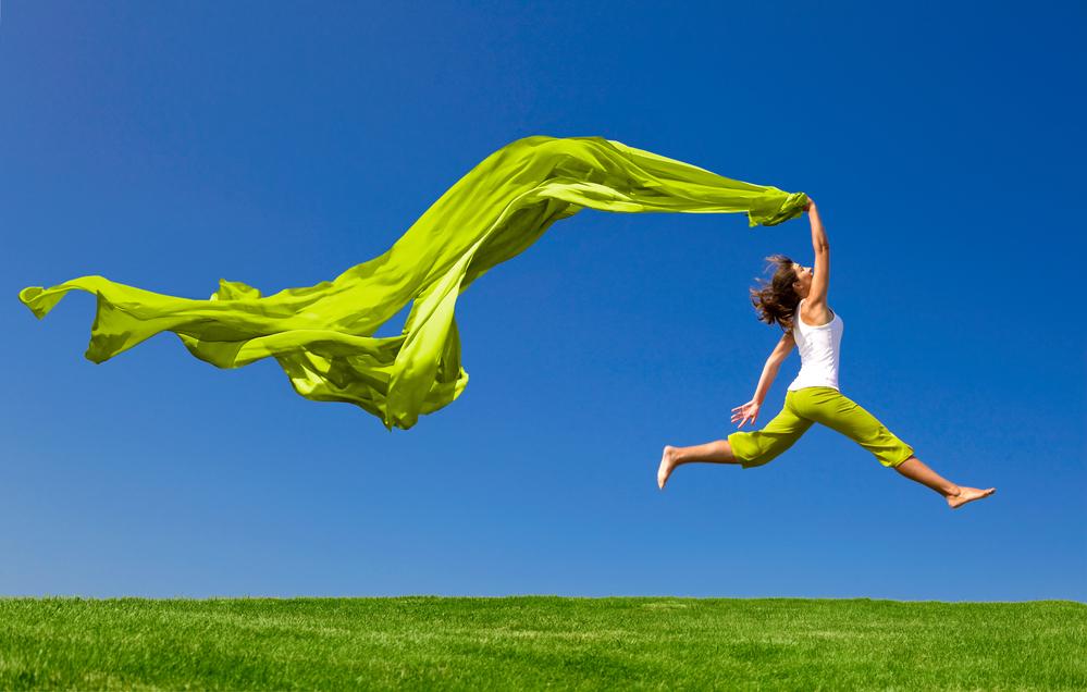 Frau springt voller Lebensfreude