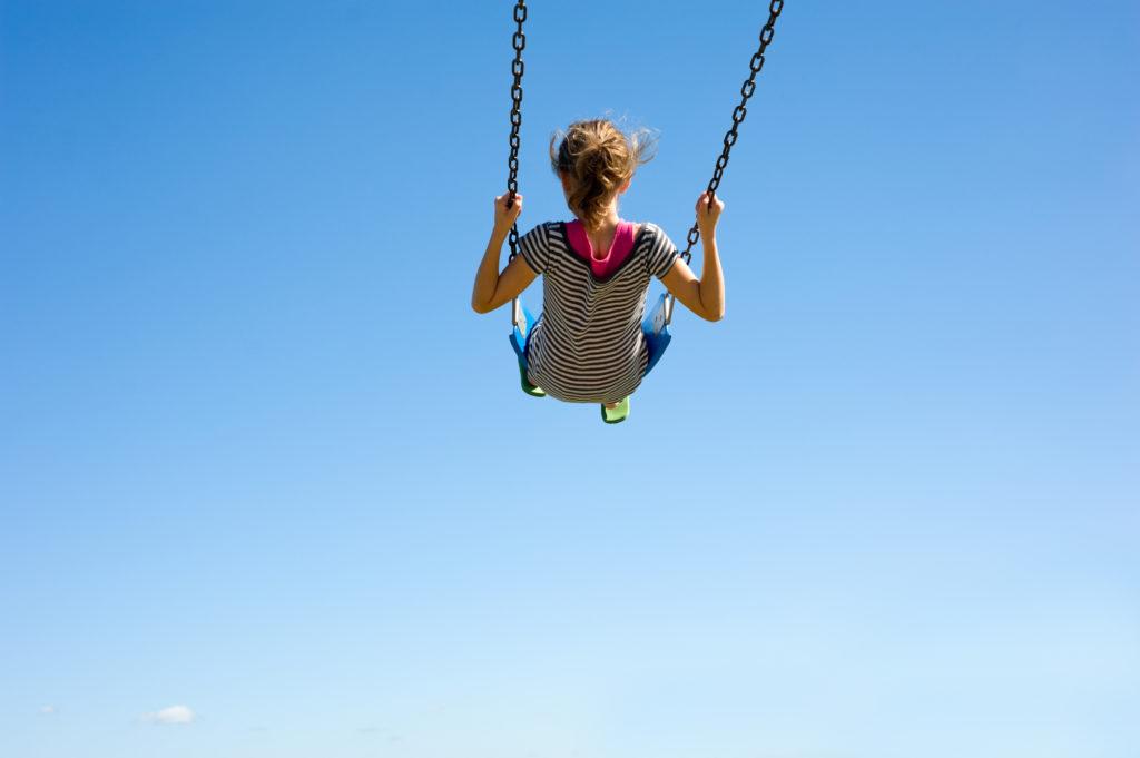 Mädchen auf einer Schaukel vor blauem Himmel