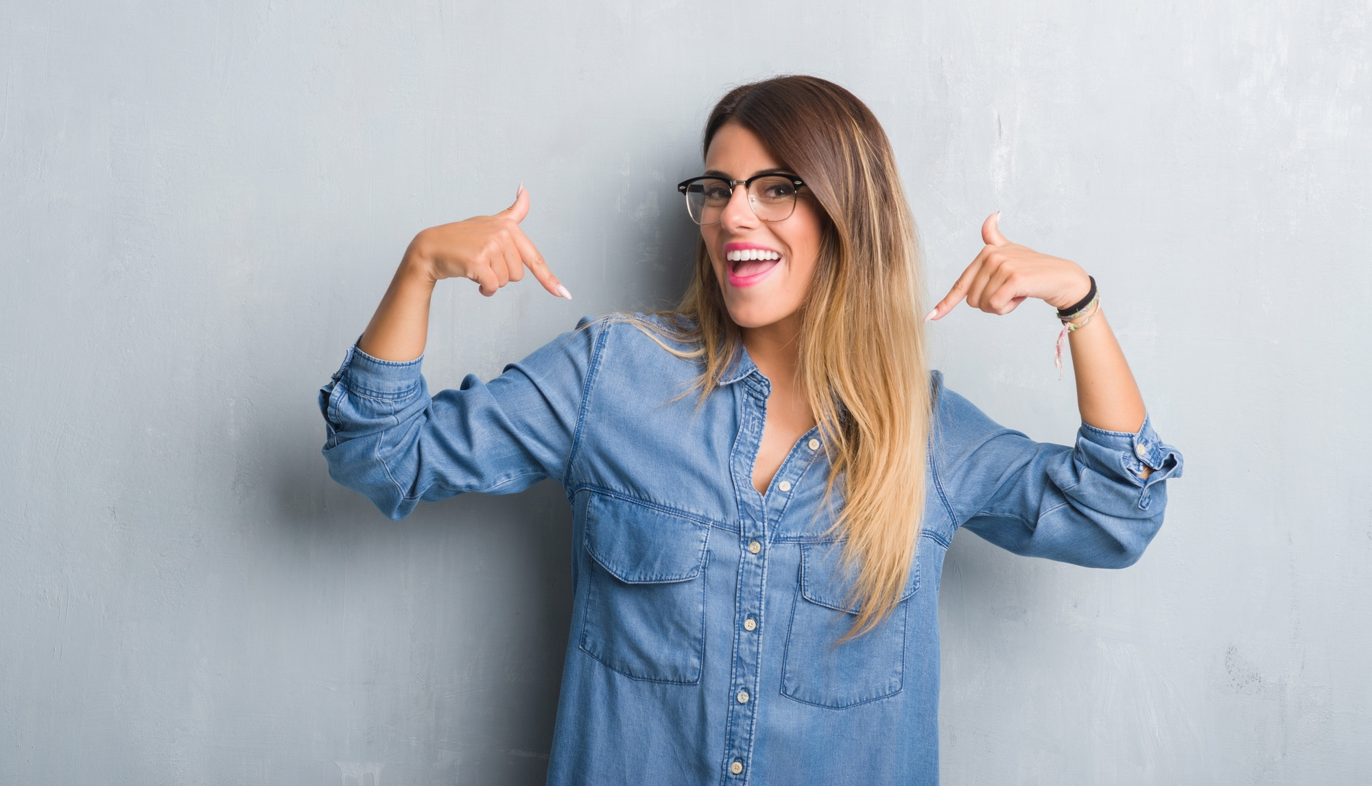 Lächelnde Frau zeigt mit beiden Zeigefingern auf sich selbst